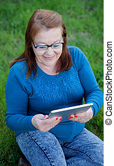 Elderly woman using a tablet while relaxing in the garden