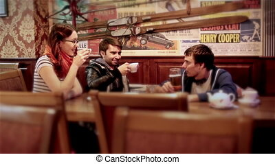 Group of young attractive cheerful friends meet in bar. Laughing discussing life