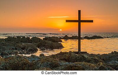 Cross On Rocks - Black cross on sea rocks as the sun departs...