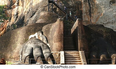 Tourists climb the stairs on Sigiriya Lion Rock Fortress in...