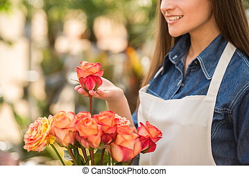 Florist - Close-up. Young female florist holding a rose in...