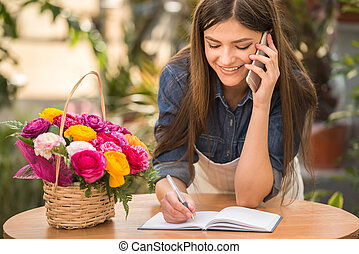 Florist - Portrait of young female florist talking on phone...