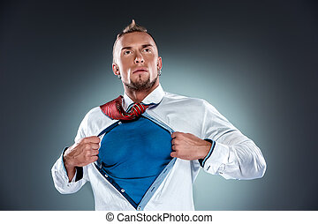 businessman acting like a super hero and tearing his shirt...