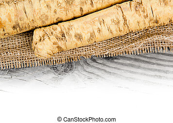 Horseradish - Photo of horseradish root on burlap with white...