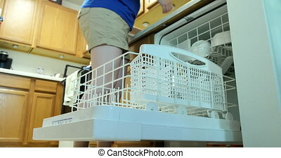 Putting dishes in dishwasher UHD 4K - Young woman filling a...