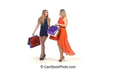 Two beautiful, happy girls with shopping bags talking about their purchases on white background, slow motion