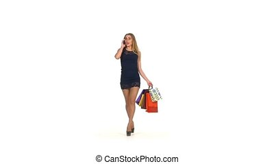 Beautiful blonde woman in short dark blue dress walking with shopping bags talking on the phone on white background, slow motion