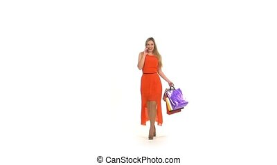 Beautiful blonde woman in long red dress walking with shopping bags talking on the phone on white background,slow motion