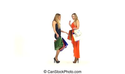 Two beautiful girls with shopping bags meet, kiss and showing their new dresses to each other on white background