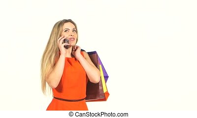 Beautiful blonde woman, long flipping hair in red dress with shopping bags talking on the phone, white background