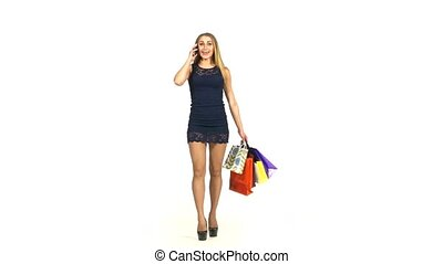 Beautiful blonde woman in short dark blue dress walking with shopping bags talking on the phone on white background