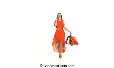 Beautiful blonde woman in long red dress walking with shopping bags talking on the phone on white background