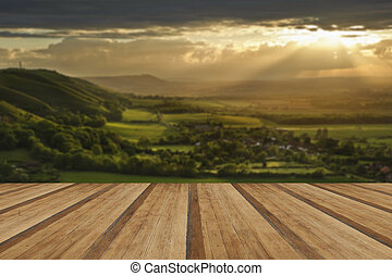Stunning countryside landscape with sun lighting side of hills a