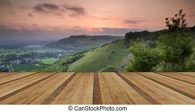 Vibrant sunrise over countryside landscape with wooden...