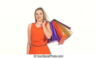 Smiling, beautiful, blonde girl in red dress with shopping bags winks and twirls on white background, slow motion
