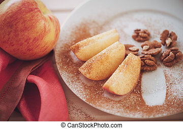 apple is sliced into wedges with cinnamon - An apple is...