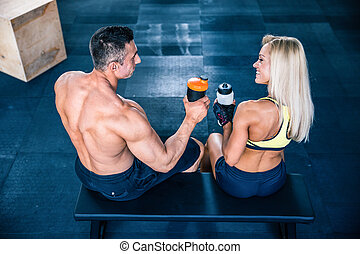Woman and man sitting on the bench at gym