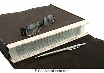 Old text book or bible with pen and eyeglasses and leather...