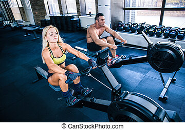 Man and woman workout on training simulator - Handsome...