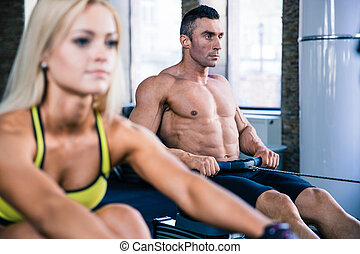 Man and woman workout on training simulator - Handsome man...