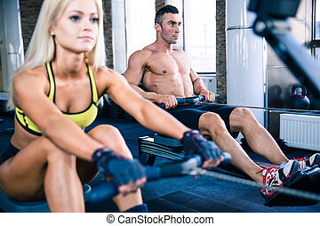 Man and woman workout on training simulator - Muscular man...