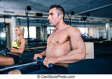 Man and woman workout on training simulator - Muscular man...