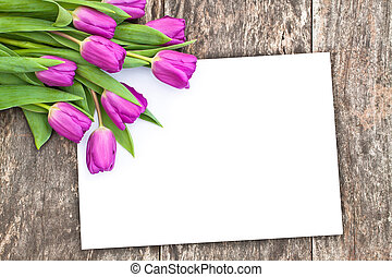 violet tulips on the oak brawn table with white sheet of...