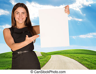 Young woman holding blank poster with nature on background...