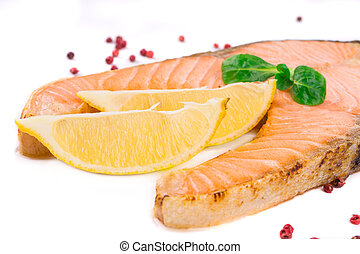 Fried salmon fillet on plate with lemon Whole background