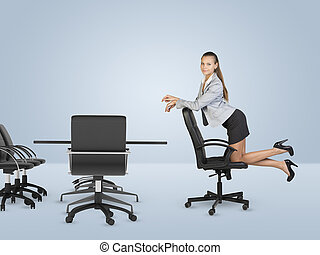 Busineswoman kneeling on chair and looking at camera...