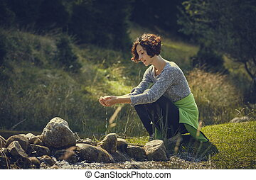 Woman washing hands in mountain stream water - Smiling young...