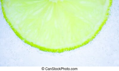 water bubbles and lime on white - Sparkling water in the...