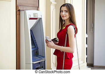 Young woman in red dress using an automated teller machine -...