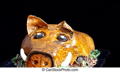 Cake in the shape of wild boar revolves on a black...