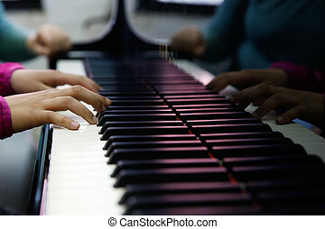 Teenager performing on a piano - Teenager playing a piano,...