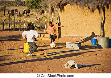African sport - African children playing football at the...