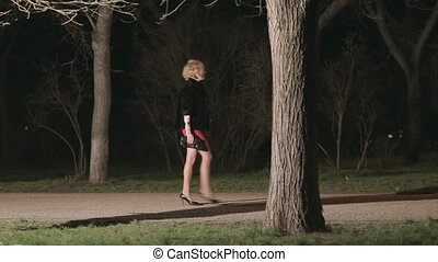 Beautiful girl in heels running through the dark park from...