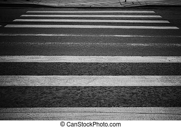 Old shabby crosswalk on black asphalt road