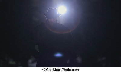Mysterious man in a black cloak and hat standing at night in...