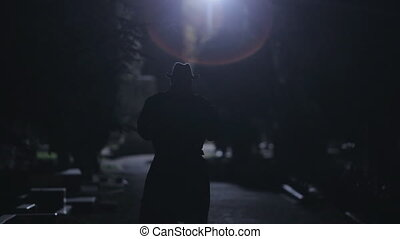 Suspicious man in a black cloak and hat going at night in...