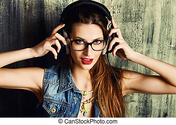 pop music - Modern girl in casual jeans clothes listens to...