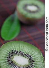The cut fruit kiwi on a bamboo napkin removed close up