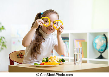 kid eating in kindergarten - kid eating healthy food in...