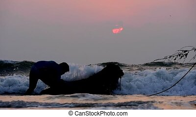 silhouettes of a boy and buffalo bathing in the sea