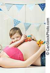 Cute boy playing with the unborn sibling - Cute little boy...