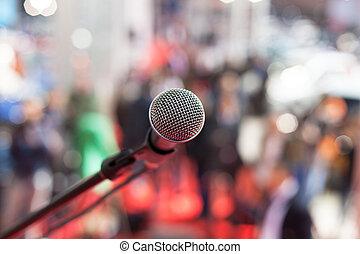 Microphone in focus against blurred audience - Microphone in...