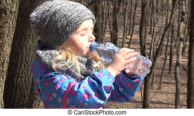Little girl drinks water from a bottle