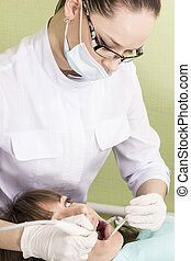 Closeup of open mouth during oral checkup at the dentist -...