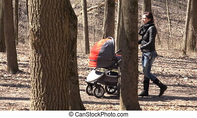 Mother Walkin in Park with Newborn Child in  Baby Carriage