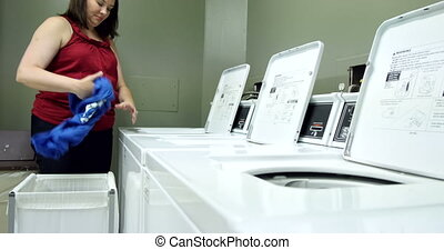Young woman doing laundry. UHD 4K